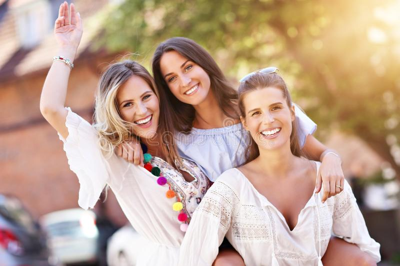 Happy girl friends hanging out in the city in summer stock images