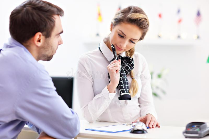 Hotel receptionist talking with guest. Picture showing receptionist talking with guest stock image