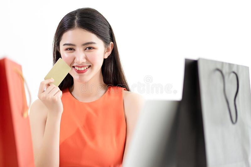 Picture showing smart attractive young asian girl holding credit card with happiness and joyful. stock photography
