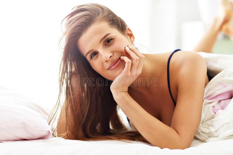 Young woman waking up in bed stock photography