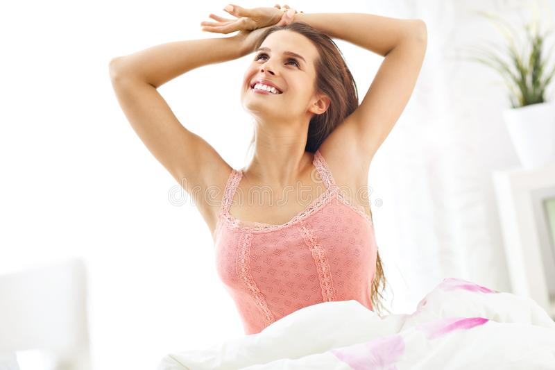 Young woman waking up in bed royalty free stock photography