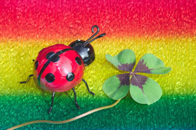 Ladybird and lucky clover on colorful crepe paper. The picture shows a ladybird and lucky clover on colorful crepe paper stock images