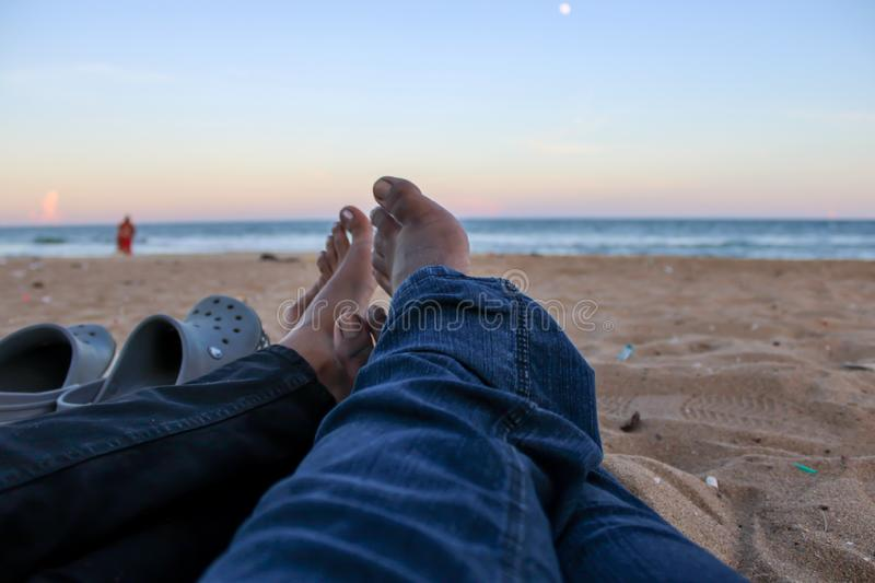 A pair of couple relaxing at the seashore. This picture shows a pair of couple relaxing their weekend on a seashore, relationship, happy, romantic, enjoy stock image