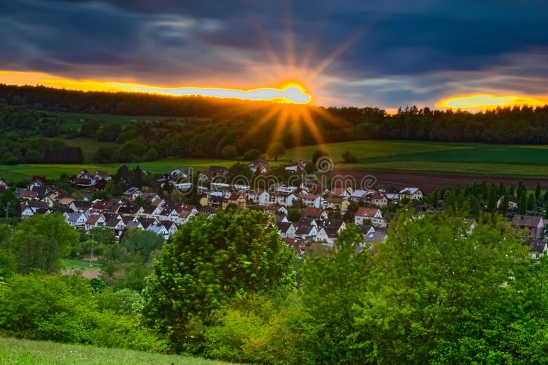 Bright sun shining over Germany. The picture shows part of the village of Rieschweiler-Mühlbach at sunset. A thick cloud cover stretches across the country royalty free stock photo