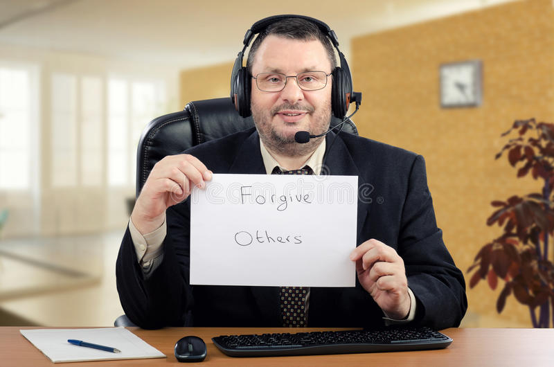 Picture of shrink with written message Forgive Others. Portrait online psychiatrist. Middle-aged man in black suit sits at the desk and holds written message royalty free stock image