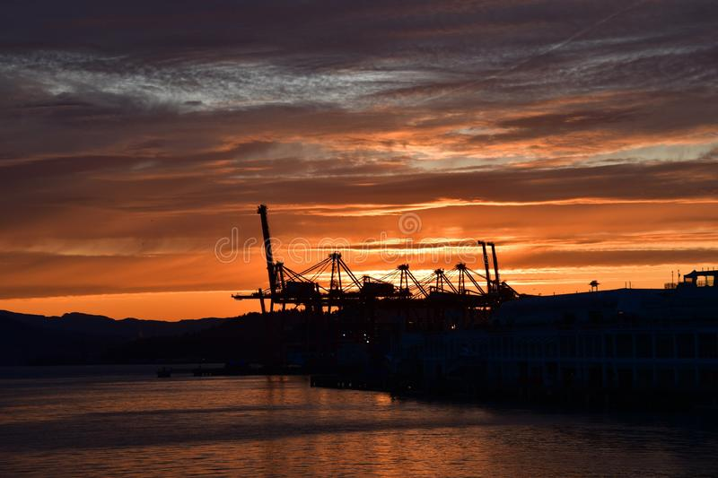 A picture of the silhouette of Metro Vancouver`s port against the sunrise. royalty free stock image