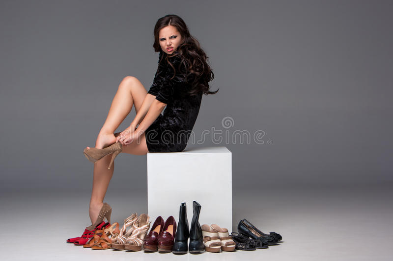 Picture of sitting woman trying on high heeled royalty free stock images