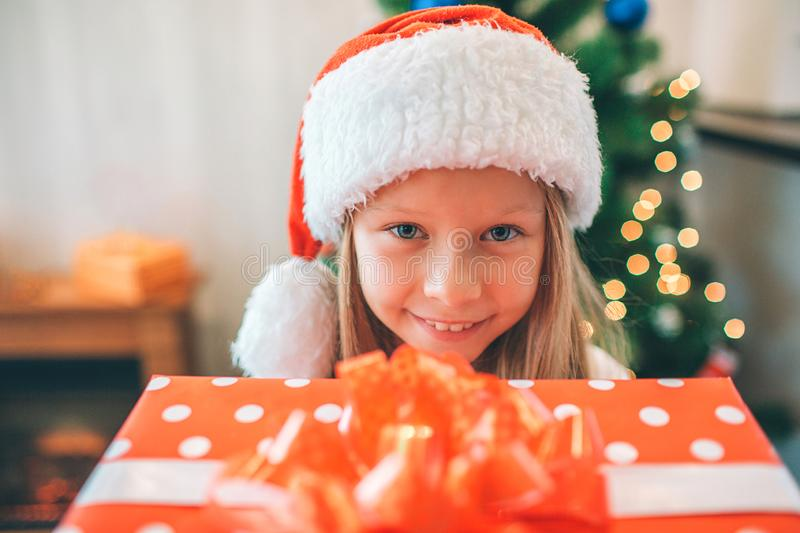 Picture of small and beautiful girl holding read box with present and looks on camera. She is happy. Girl wears royalty free stock photos