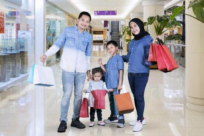 Smiling Muslim family hold shopping bags in mall stock image