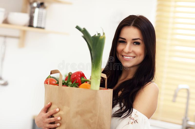 Portrait of smiling young housewife in modern kitchen royalty free stock photos