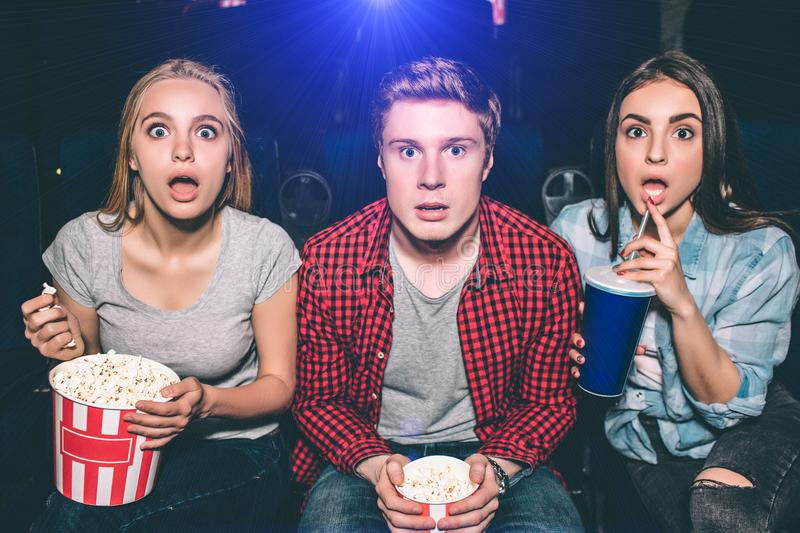A picture of surprised and amazed young people looking to the camera. Blonde girl is holding a basket of popcorn while stock photography