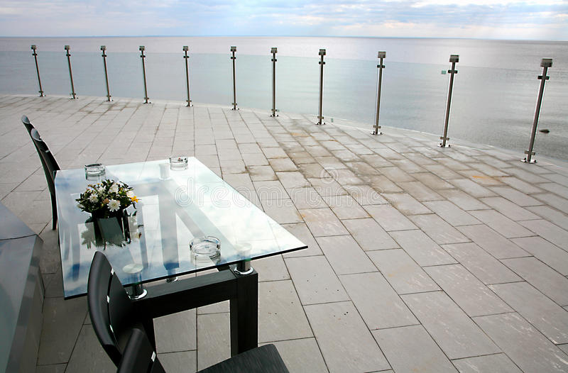 The picture table with chairs standing on the outdoor terrase overlooking the sea and a cloudy sky. Photo floral bouquet black table with glass top with three stock images