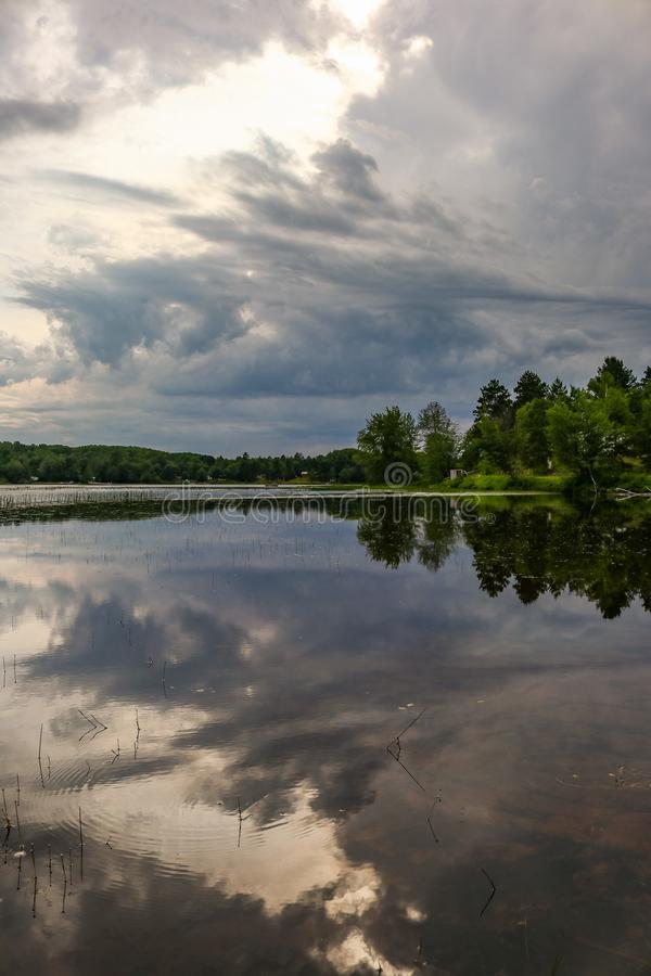 Dramatic cloudscape over the rivers water with trees. Picture taken with Canon 80d of dramatic cloudscape over the rivers water with trees stock image