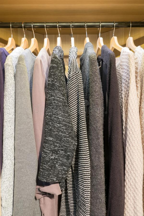 Picture taken straight into a wardrobe. Warm winter sweaters stock photography