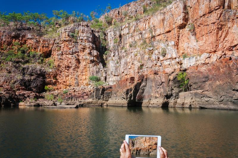 Picture taking at Katherine river gorge in Nitmiluk National Park, Australia. One person is taking a picture of the gorgeous sandstone walls of the Katherine stock photography