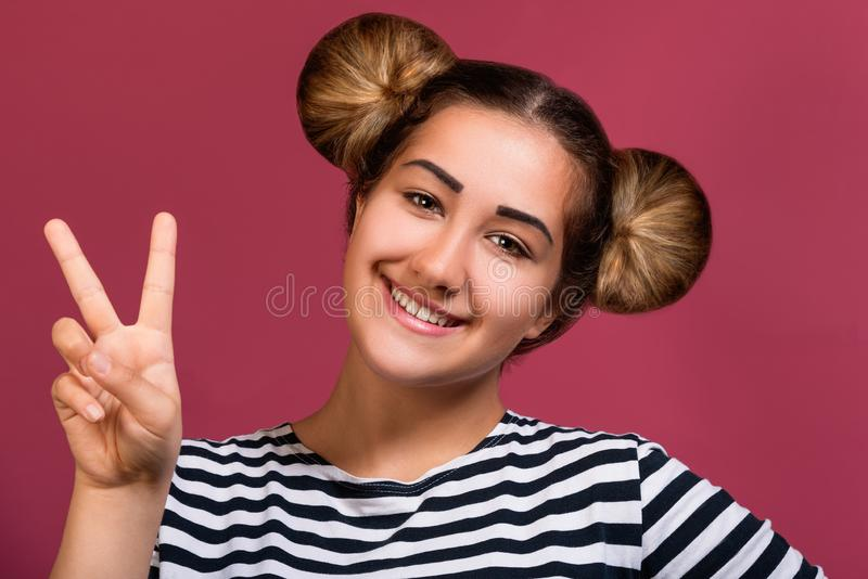 Picture of young hipster girl with funny hairstyle doing victory sign gesture isolated over pink background stock images
