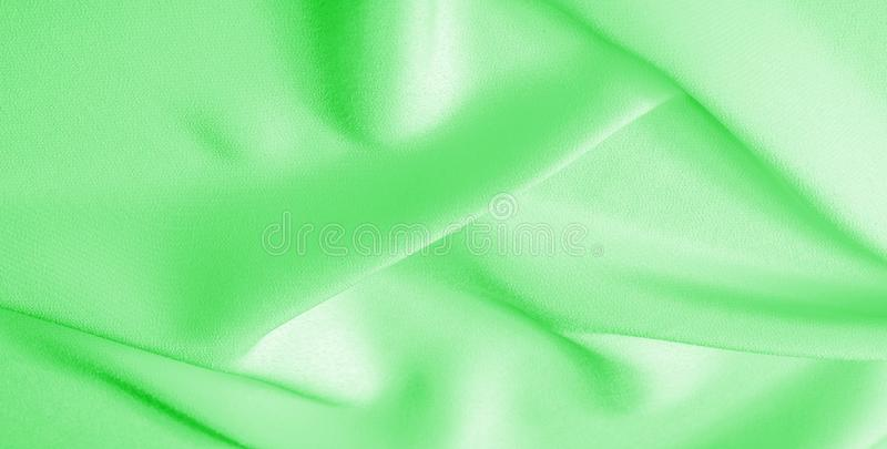 Picture. Texture, background. green emerald silk fabric. This medium / silky silk fabric has a wonderful shine with slight color. Variations to give the look a stock image