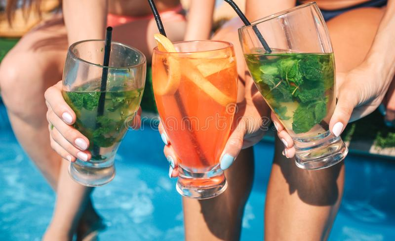 Picture of three colorful cocktails women hold in hands. They sit at edge of swimming pool and keep legs in water. stock photos