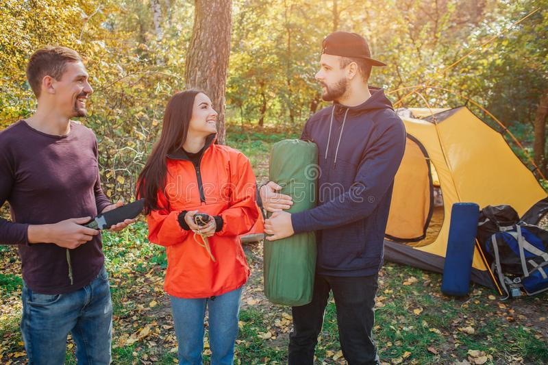 Picture of three friends in forest. Young woman smiles and looks at bearded guy. He holds sleeping bag. Another young royalty free stock photo