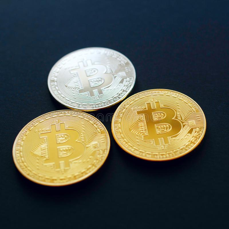 Picture of three gold bitcoin over black background. Digital mon stock images