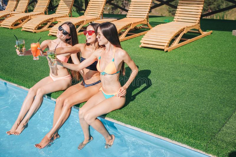 Picture of three models sits at edge of swimming pool and relax. They hold three glasses of cocktails close. Young women stock image