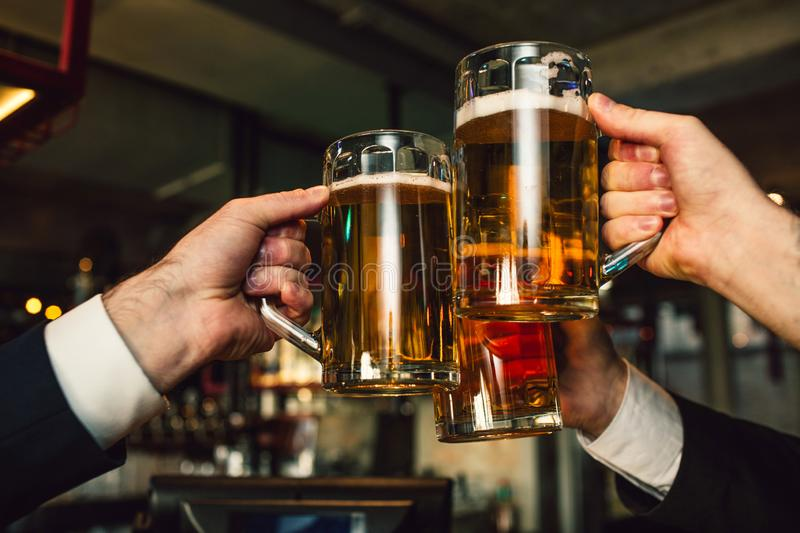 Picture of three mugs of beer in men hands. People wear suits. They are in bar. royalty free stock image