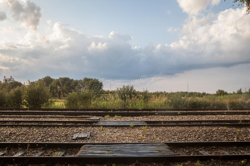 Railway tracks, rails and platforms in a rural train station in Uljma, Serbia, taken during a sunny sunset after a rain. Picture of the train tracks in the stock photography
