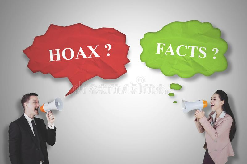 Two business people shouting fact and hoax. Picture of two business people using a megaphone while shouting fact and hoax stock images