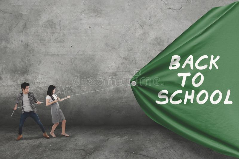 Two students drag text of back to school. Picture of two college students using a chain to drag text of back to school on the green banner royalty free stock images