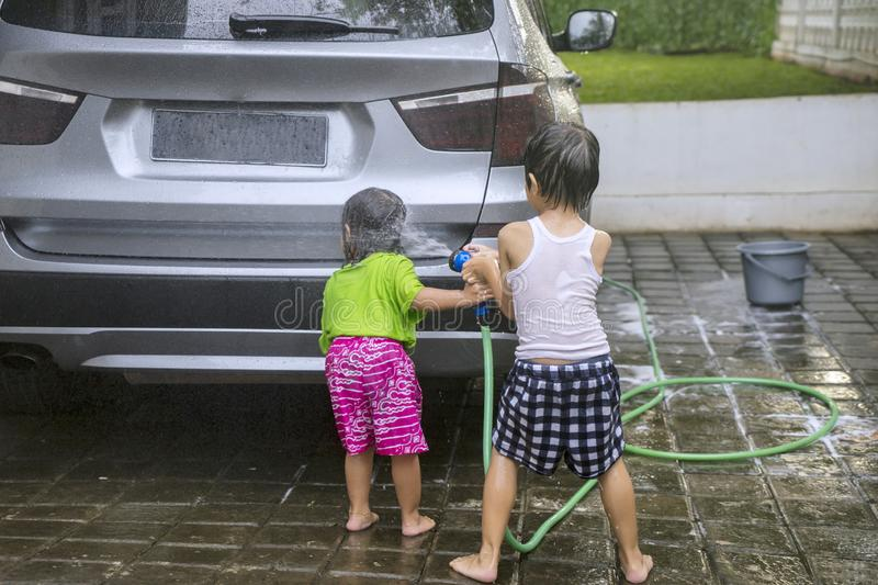 Two little kids washing a car at home royalty free stock photos