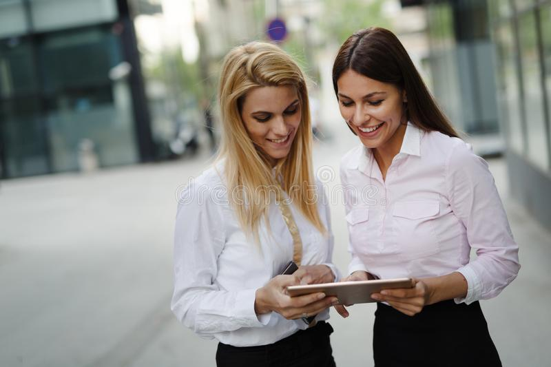 Picture of two young beautiful women as business partners. Standing outside royalty free stock photo