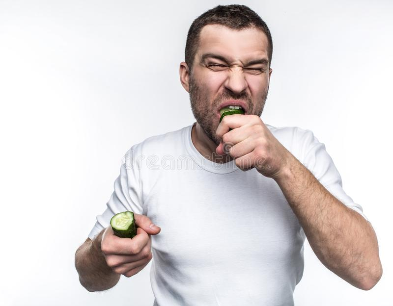 A picture of vegetarian biting a big piece of green and good cucumber. He is biting hard. Also he is holding the other royalty free stock photo
