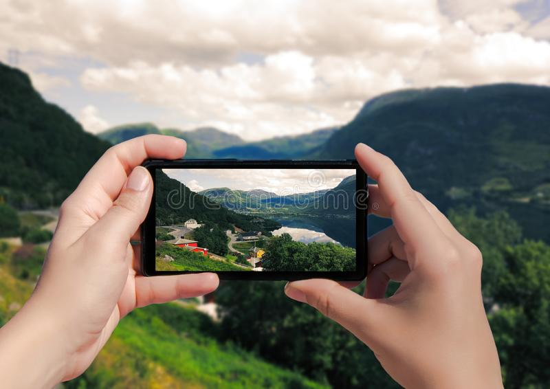 Picture of villagei in Norway on mobile phone. Female take picture houses and port in Lysefjorden royalty free stock photography