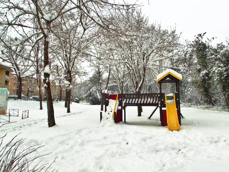 Kids` playground with yellow and red slide covered in snow stock images