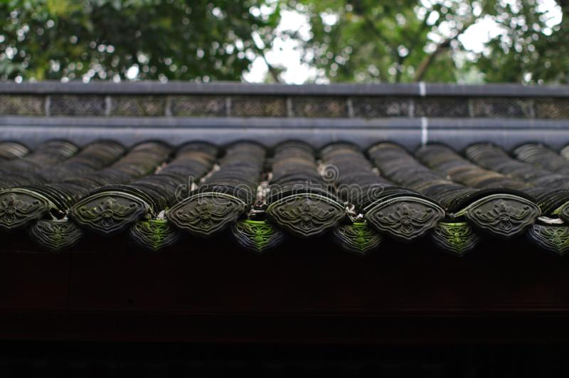 Eaves in a wet weather. The picture was taken using Pentax A50 1.2 lens in Chengdu, China. The carve on the tiles are bats, which is homophonic to happiness in royalty free stock images
