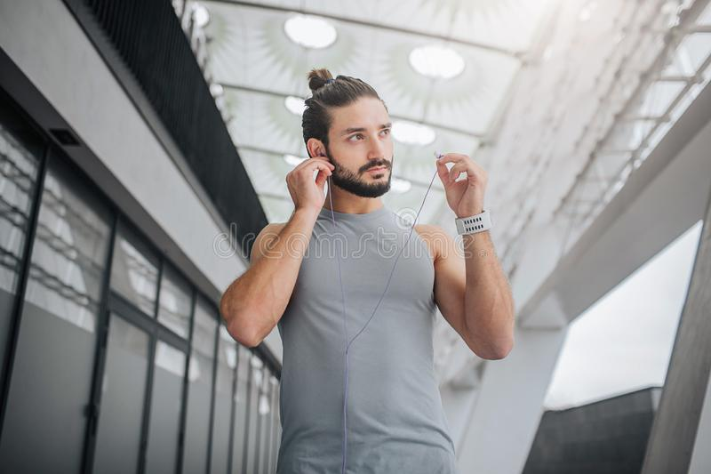 Picture of well-built and handsom bearded young man looks to right. He puts headphones in ears. Guy walks on stadium. He. Is alone royalty free stock photos