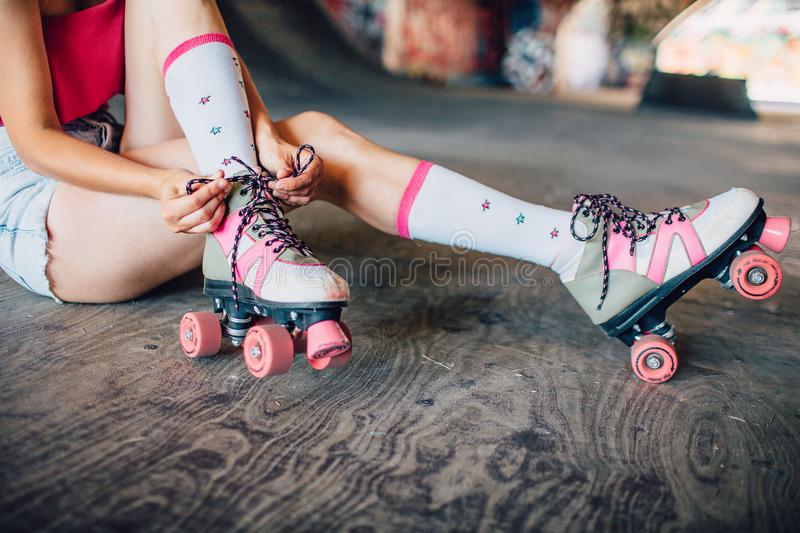 A picture of well-built and slim legs of one girl. She is sitting on concrete and tying laces on rollers. They are pink royalty free stock photo