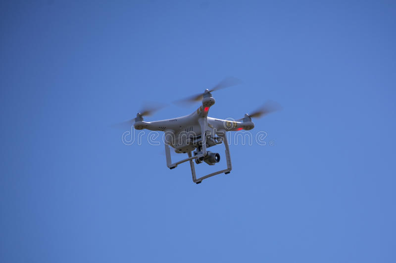 Picture of a white camera drone flying in blue sky. Flying drone with camera royalty free stock photo