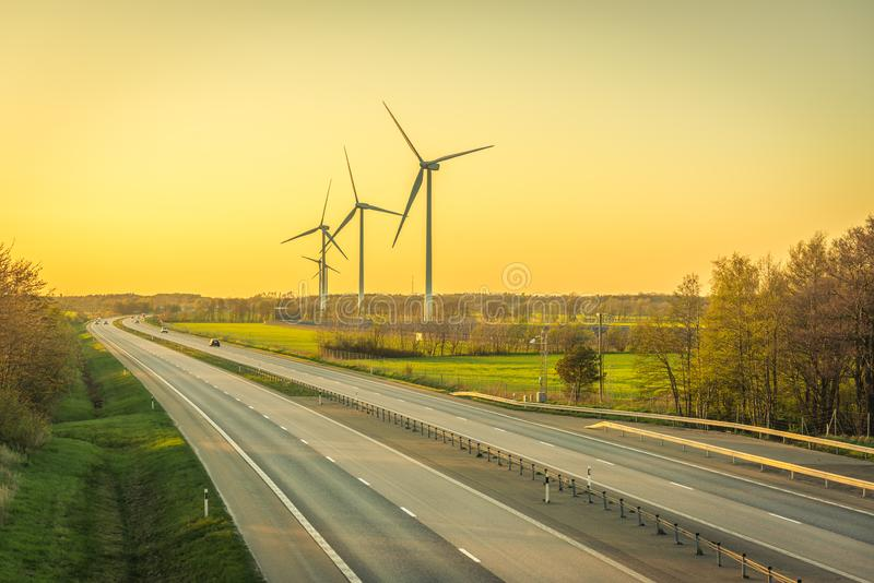 Picture of wind farm generators in the green field close to the road with cars at the sunset royalty free stock image
