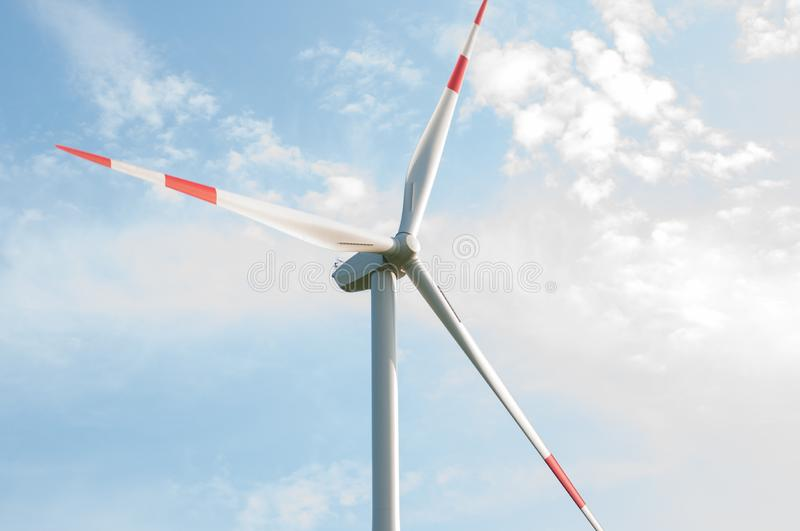 A picture of a windmill overlooking a beautiful blue sky. Rotate, pinwheel, white, weather, energy, generation, turbine, ecological, environmental stock images