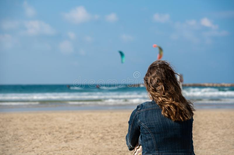 Picture of a woman on the beach looking at two kitesurfers in the sea. Woman seated on the beach contemplating the view. Kitesurfers in the background stock photos