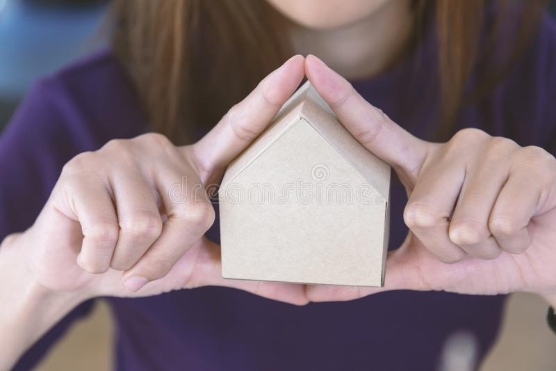 Picture of woman holding paper house model in her hands. In house insurance, family, real estate concept stock photos