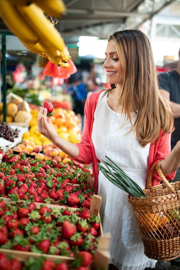 Picture of woman at marketplace buying vegetables royalty free stock images