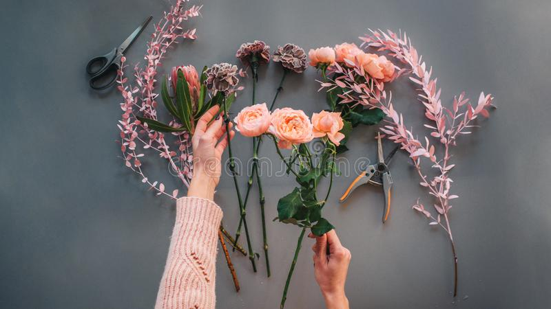Picture of woman`s hands holding orange roses. Other meadow flowers and plants lying together with nippers. on. Grey background stock photos