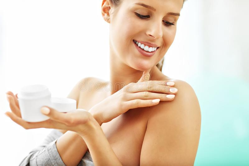 Woman using body lotion on her skin. Picture of woman using body lotion on skin at home royalty free stock photos