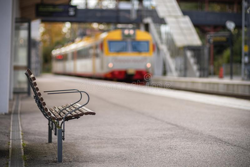 Picture of wooden bench on the train station with blurred train on the background stock image