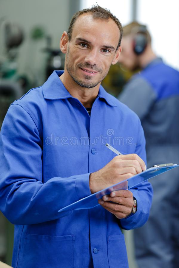 Picture worker in blue overalls holding clipboard. Picture of a worker in blue overalls holding clipboard stock photos