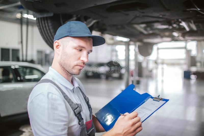 Picture of worker standing in garage. He is serious. Guy holds plastic folder with papers and sighning them. Man wears royalty free stock image