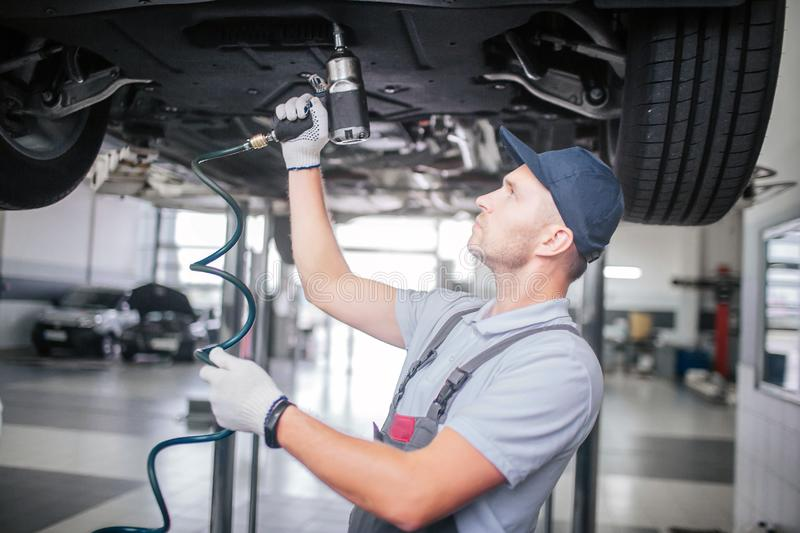Picture of younf man standing and working underneath car. He looks up. Guy holds and uses drill. He works in white royalty free stock photo