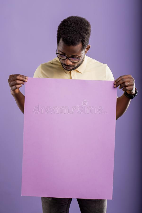 Picture of young african american man holding blank board on violet background stock image